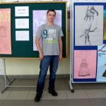 Jeden z uczestnikow na tle zgloszonych do konkursu plakatow.